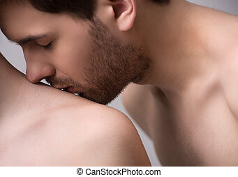 Kissing her shoulder. Close-up of handsome young men kissing...