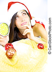 Beautiful female santa claus thinking about Christmas with...