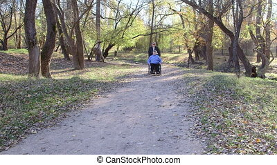 disabled senior in wheelchair - Caregiver walking with...