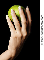Green apple in manicured hand