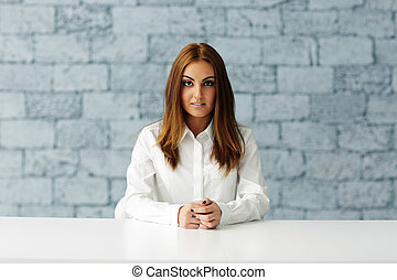 Young serious businesswoman sitting at the table in office