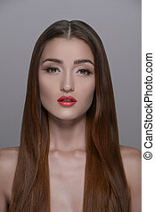 Pure beauty. Portrait of beautiful girl with smooth gloss long hair standing isolated on grey