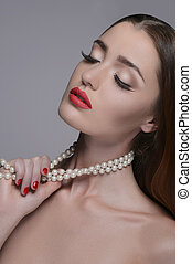 Women with pearl necklace. Portrait of beautiful women touching her pearl necklace and keeping eyes closed while isolated on grey