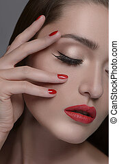 Beautiful manicure. Portrait of beautiful women touching face with hand and keeping eyes closed while isolated on grey