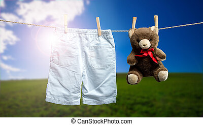 Baby boy pants, a teddy bear on the outdoor clothesline