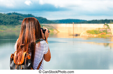 tourist taking photo pictures of dam in Thailand