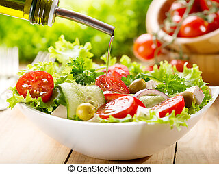 olive oil pouring over salad - olive oil pouring into bowl...