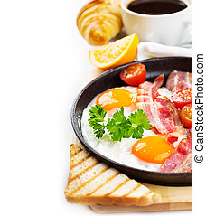 pan of fried eggs, bacon and vegetables on white background