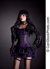 Romantic gothic girl in purple and black outfit, studio shot...