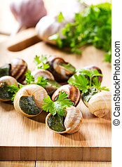 escargots with parsley on wooden table