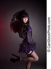 Portrait of gothic Lolita girl with umbrella, studio shot on...