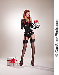 Beautiful redhead pin-up style girl holding gift box,...