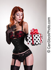 Portrait of a beautiful redhead pin-up style girl holding gift box, Christmas or holiday theme