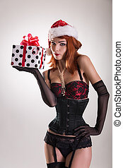 Pretty girl wearing pinup outfit and Santa Claus hat,...