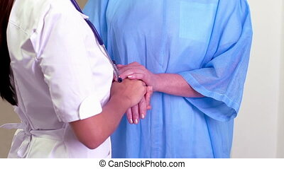 To care - Young nurse holding the hand of a mature patient...