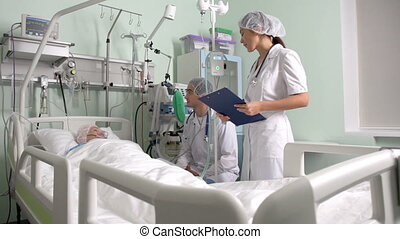 Post-surgery - Doctor and nurse taking care of a...