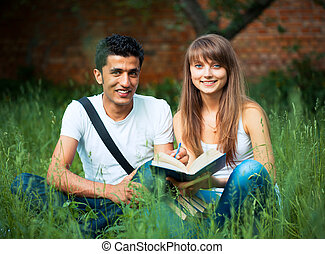 Two students studying in park on grass with book outdoors -...