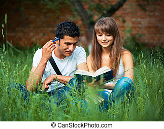 Two students studying in park on grass with book outdoors