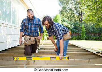 Construction Workers Looking At Spirit Level On Plank -...