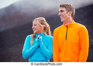 Young attractive athletic couple, wearing sporty cloths on...