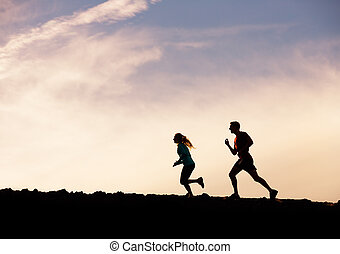 Silhouette of man and woman running jogging together into...