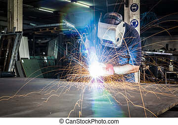 Worker welding in steel workshop with bright light and...