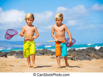 Happy young kids playing at the beach on summer vacation,...