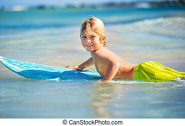 happy young boy in the ocean on surfboard - Young surfer,...