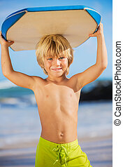 Happy Young boy having fun at the beach on vacation, with...