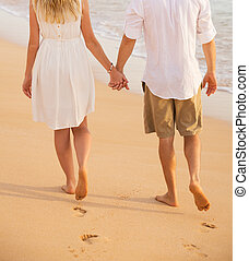 Romantic couple holding hands walking on beach at sunset....