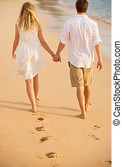 Romantic couple holding hands walking on beach at sunset. Man and woman in love. Footprints in the sand.