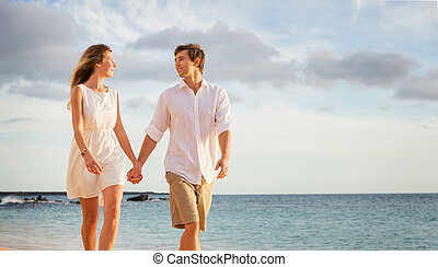 Romantic happy couple walking on beach at sunset Smiling...