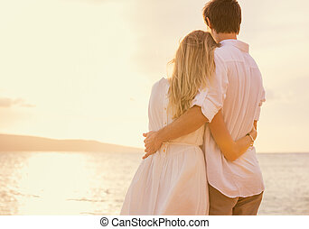 Happy romantic couple on the beach at sunset embracing each...