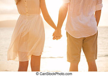 Couple holding hands at sunset on beach Romantic young...