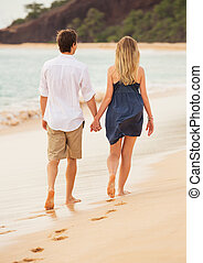 Romantic happy couple walking on beach at sunset. Smiling holding hands. Man and woman in love
