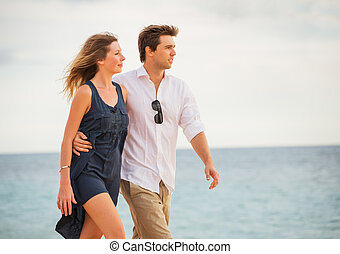 Romantic happy couple walking on beach at sunset. Smiling