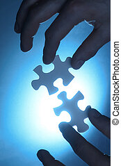 Contact - hands trying to fit two puzzle pieces together