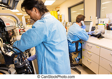 Trouble shooting lab equipment - Group of lab technicians...