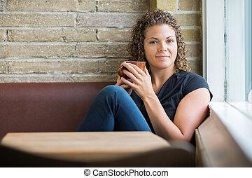 Woman With Coffee Mug Sitting In Cafeteria - Portrait of...