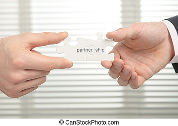 Partnership - Two people connect puzzle pieces symbolizing...
