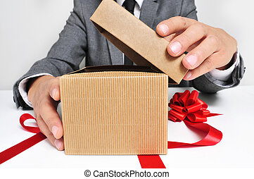 man in suit opening a gift - man wearing a suit sitting in a...