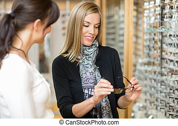 Woman Examining Eyeglasses With Salesgirl - Young woman...