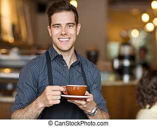 Happy Waiter Holding Coffee Cup In Cafeteria - Portrait of...