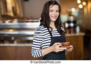 Beautiful Waitress Holding Coffee Cup In Cafeteria -...