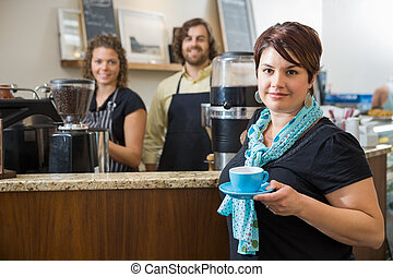 Customer Holding Coffee Cup With Workers At Café - Portrait...