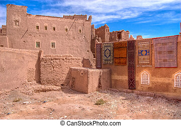 casbah and carpets - ouarzazate old casbah with colorful...