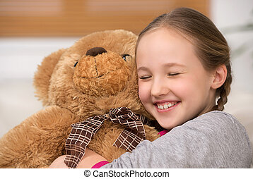 Cute girl with toy bear. Cheerful little girl hugging toy...