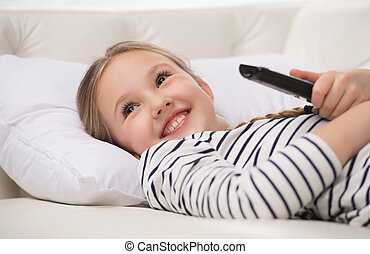 Girl watching TV. Cheerful little girl holding remote...