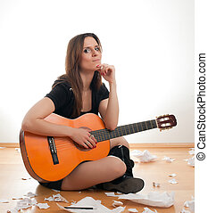 woman with guitar - young woman with guitar sitting on floor...