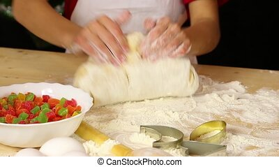Kid hands kneading the dough on the table